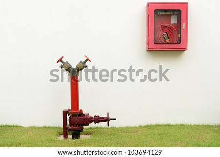 The red fire hydrant and fire hose next to the building.