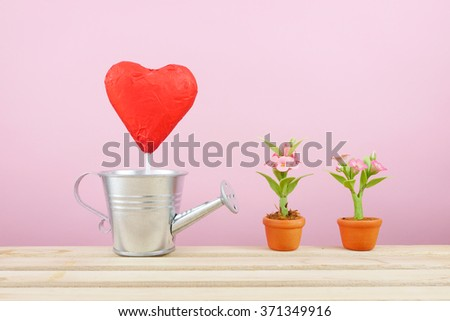 The red foiled chocolate heart stick with small silver watering can and mini fake flower in brown plant pot on wooden tray for Valentine's day.