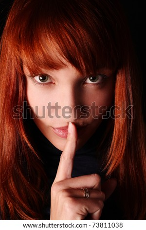 The red-haired girl has brought a forefinger to lips