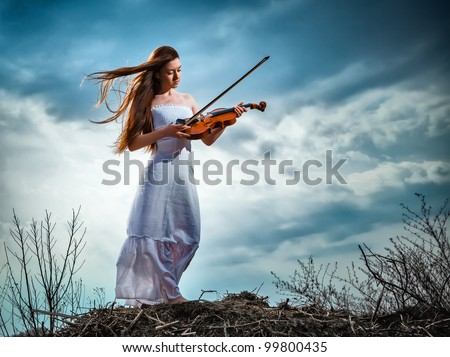 The red-haired girl with a violin outdoor