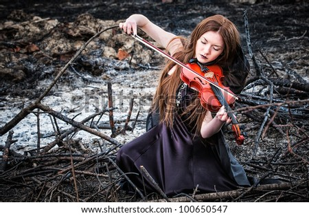 The red-haired girl with a violin sitting on the ashes