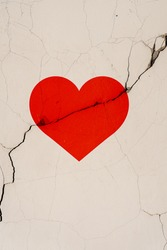 The red heart symbol is located on a crack in the wall. Vertical foto