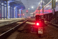 The red light of the traffic light signals a redirection signal for trains.  Train Station.  Night photo.