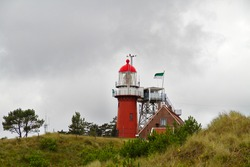 The red lighthouse and next to it the lighthouse keeper's house in het dunes of the Dutch island of Vlieland