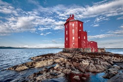 The red lighthouse of Kjeungskjaer, Norway, on rocky islet against a bright blue sky with white clouds. A woman with binoculars looks out over the ocean from a railed platform of the lighthouse.
