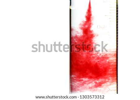 The red liquid poured in the glass utensil, in transparent liquid. The mixing of different color liquids. The concept of medical theme on the isolated white background. #1303573312