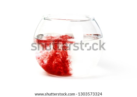 The red liquid poured in the glass utensil, in transparent liquid. The mixing of different color liquids. The concept of medical theme on the isolated white background. #1303573324