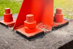 The red metal support is bolted to the concrete base with large bolts. Fixing a tower or tower to the ground. Close-up