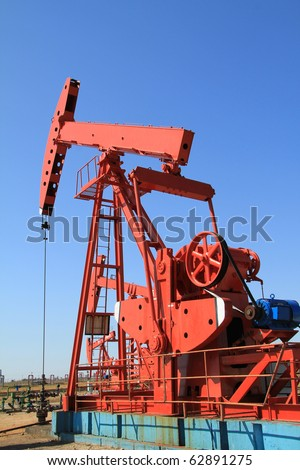 The red oil pump jack on blue sky