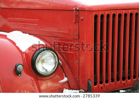 The red old car under a snow