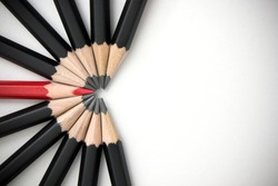 The red pencil is prominent and is surrounded by a black pencil. Leadership, uniqueness, think different, teamwork business success