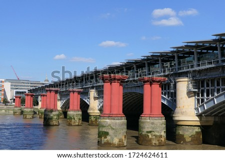 The red pillars of the old Blackfriars railway bridge over the River Thames in London with the modern bridge
