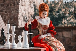 The Red Queen is playing chess. Red-haired woman in a chic vintage dress. Fashion Photo