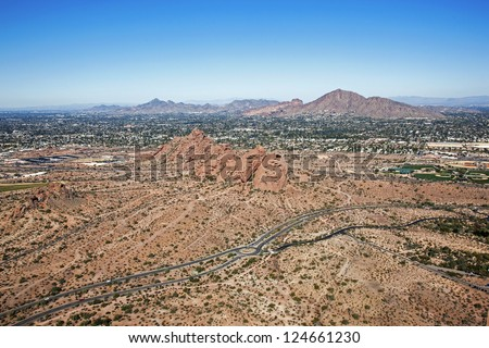 The Red Rocks of Phoenix, Arizona at Papago Park with Camelback Mountain and Piestewa Peak in the distance - stock photo