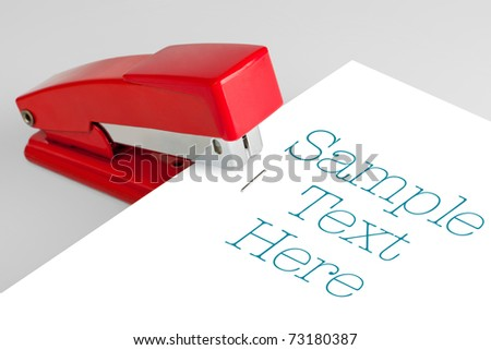 The red stapler lies on a white background