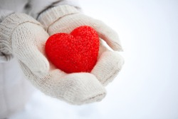 The red textured heart lies on the palms. I give you heart. Valentine's Day.