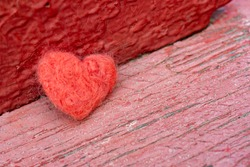 The red toy heart lies on the background of an old wooden surface. A symbol of love, loneliness, melancholy and depression.
