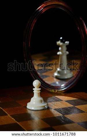 the reflection in the mirror of a chess Queen and pawn #1011671788