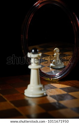 the reflection in the mirror of a chess Queen and pawn #1011671950