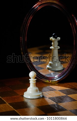 the reflection in the mirror of a chess Queen and pawn #1011800866