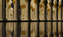 The reflection of the pillars of the grand mosque in the fountain waters.