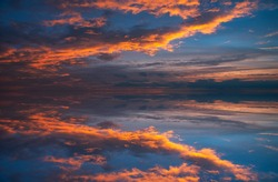 The reflection of the sunset, sunset glow and blue sky on the calm water after sunset