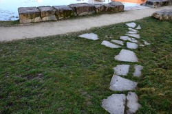 the relaxation zone by the water of the pond with a stone staircase in the park is a stepped stone path made of beige sandstone. in the foreground is a sidewalk of individual flat stones in the lawn