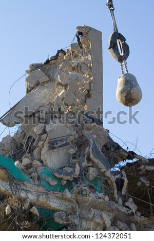 The remains of a demolished factory building, with wrecking ball hanging amidst the wreckage.