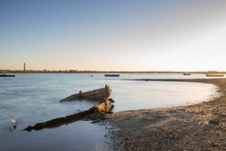 The remains of an old fishing boat sunk in the sea flooded at dawn in a bay where there are more small boats moored.
