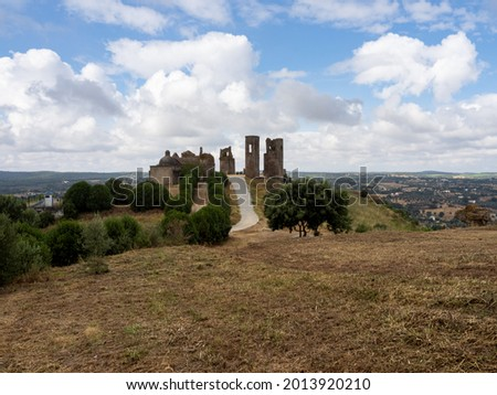 The remains og the Palace of the Mayors and the Church of São João Baptista in the Montemor-o-Novo Castle, with a field in the foreground. Montemor-o-Novo, Portugal. Foto stock ©