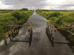 the remnants of a wooden bridge over the glare of clouds full of river black water