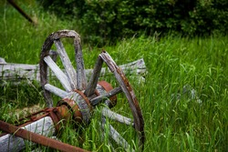 The remnants of an old wooden and rusty steel wagon, including a wood wagon wheel, are lying in tall grass in a rural setting.