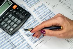 The report summarizes the results of business operations, pen, calculator on desk of investor. Financial business statement report