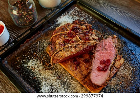 The restaurant serves an unusual meat directly on the baking sheet, designed for a big company, sauce can be different but perfect dish for the sauce from the berries with the addition of hot peppers