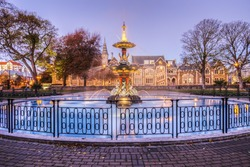 The restored Peacock Fountain in Christchurch Botanic Gardens at twilight with the Arts Centre (former University) in the background.
