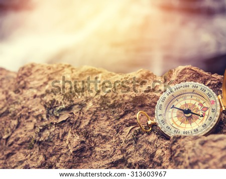 The retro compass on the rock with waterfall blurred background and sunlight. Vintage style photo.