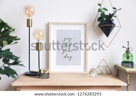 The retro mock up photo frame on the vintage wooden shelf , hanging plant in design pot, green sprinkler gold pyramid and table lamp. Concept of minimalistic shelfie.