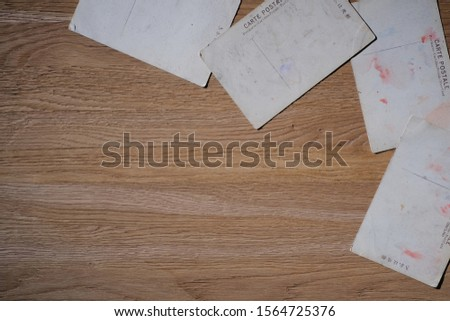 """The reverse side of old postcards on a wooden table. The inscription """"Postcard"""" in French, German, Italian, English, Russian and Japanese. Top view, macro. #1564725376"""