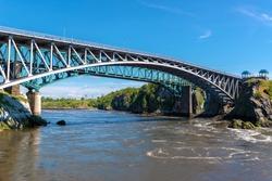 The Reversing Falls bridge in Saint John, New Brunswick, Canada, over the Saint John river. River slowly flowing outward. Train bridge behind, blue sky above. Low angle view.