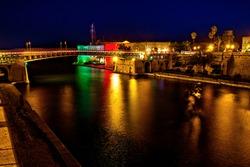 The revolving steel bridge of Taranto, Puglia, Italy, on the water channel, seen illuminated at night, long exposure photo