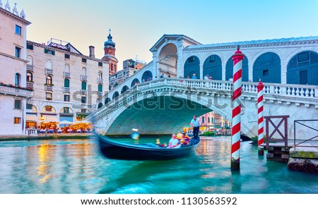 The Rialto Bridge in Venice in the evening, Italy. Long exposition - Gondola and people in the motion blur