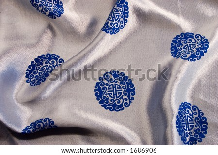 The rich blue and silver silk background with chinese or japanese emblems and design provides a colorful cultural backgound, texture or brush.