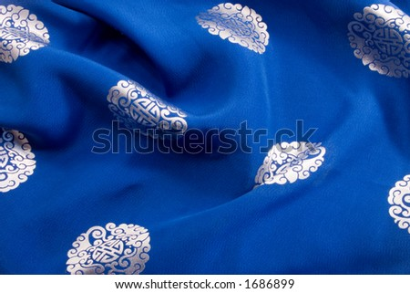 The rich blue silk background with chinese or japanese emblems and design provides a colorful cultural backgound, texture or brush.
