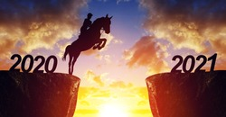 The rider on the horse jump from 2020 to 2021 at sunset. Happy New Year concept.