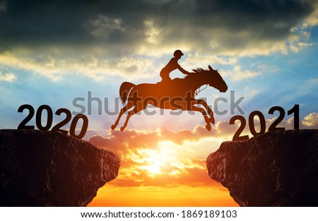 The rider on the horse jump from 2020 to 2021 at sunset. Happy New Year concept. Stockfoto ©