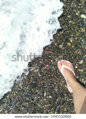 the right leg of a man in a white rubber slipper for swimming stands on the mottled surface of sea pebbles at the coastal edge with white foam of the incoming wave, diagonal co-position, space for tex Photo stock ©