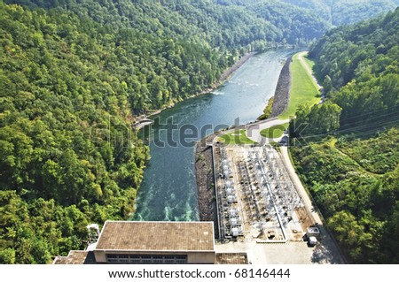 The river beside a large power plant below a dam.