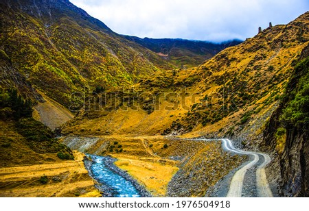 The road along the stream in the mountains. Winding trail road in mountains. Mountain winding trail view