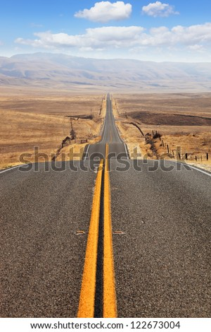 The road goes the distance. Perfectly smooth highway across the endless desert