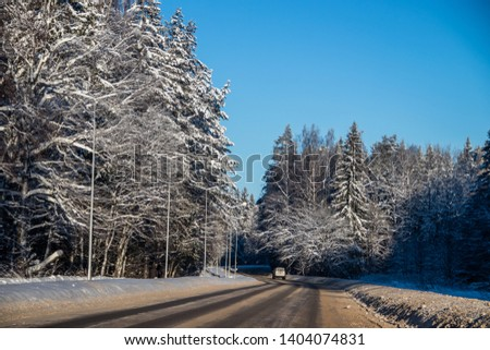 The road in the winter forest. Snow picture. Branches of trees in the snow hang over the road.
